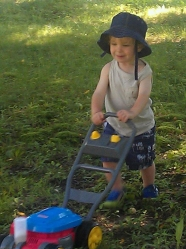 "Our nephew William happily ""mowing"" the lawn."