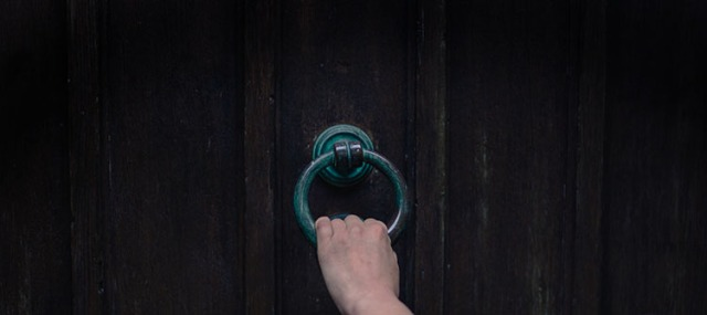 Female hand touching knocker